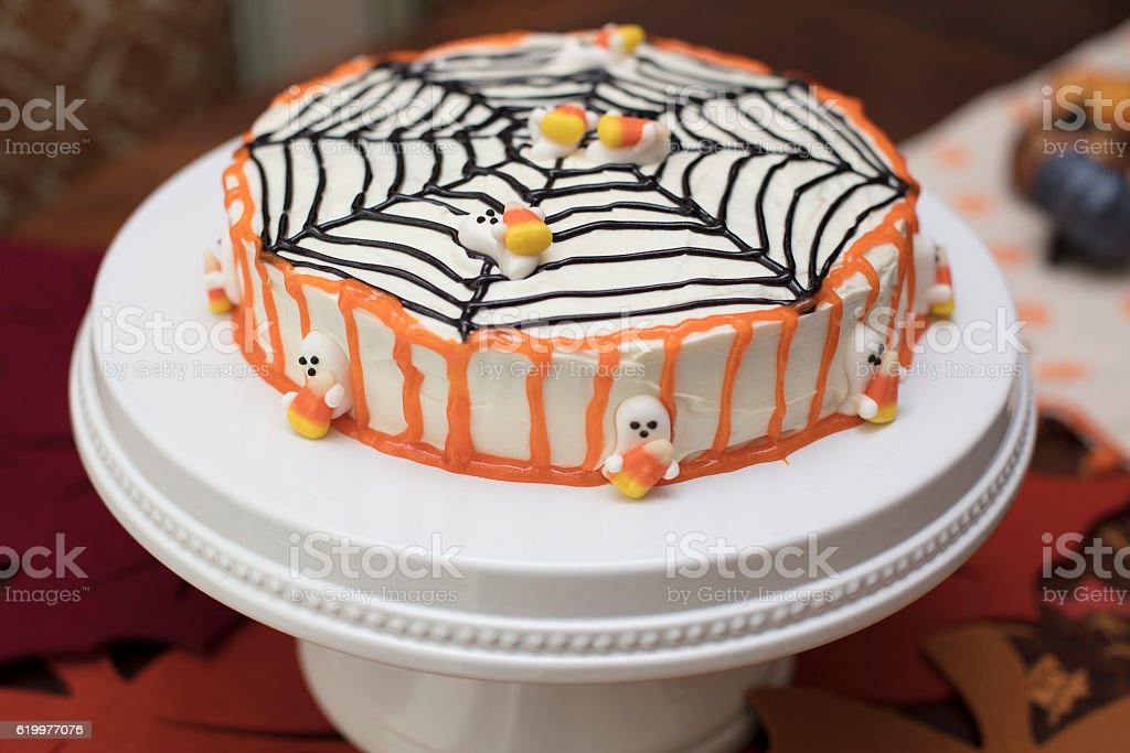 Halloween cake with orange, black and white frosting with a spider...