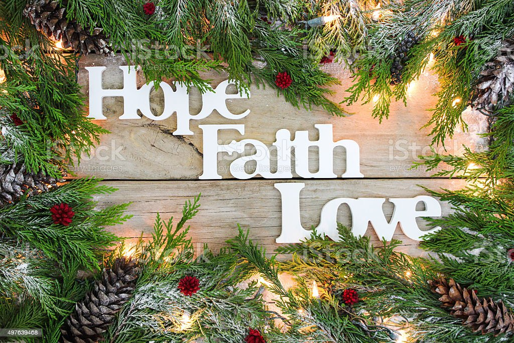Holiday Hope, Faith, Love sign with garland border stock photo