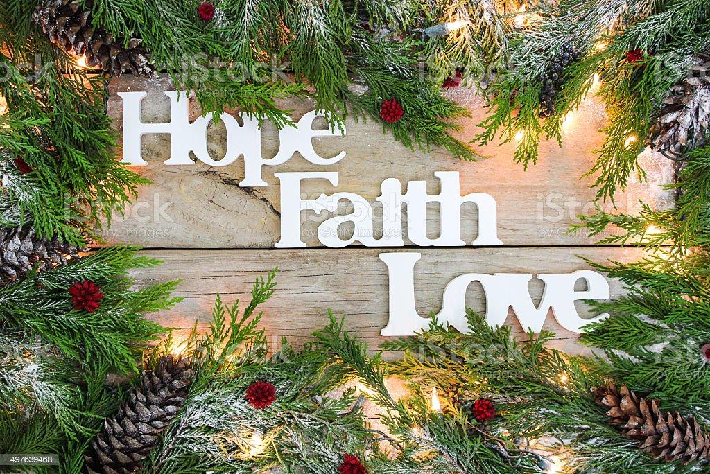 Holiday Hope, Faith, Love sign with garland border stock photo
