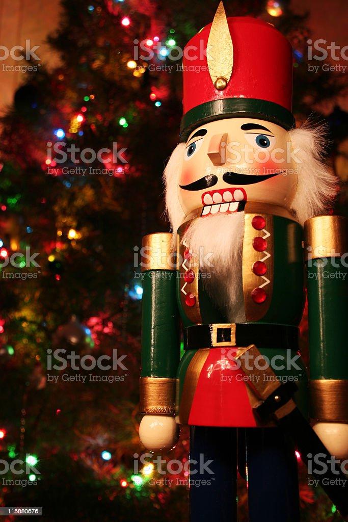 A holiday nutcracker and a Christmas tree on the back stock photo