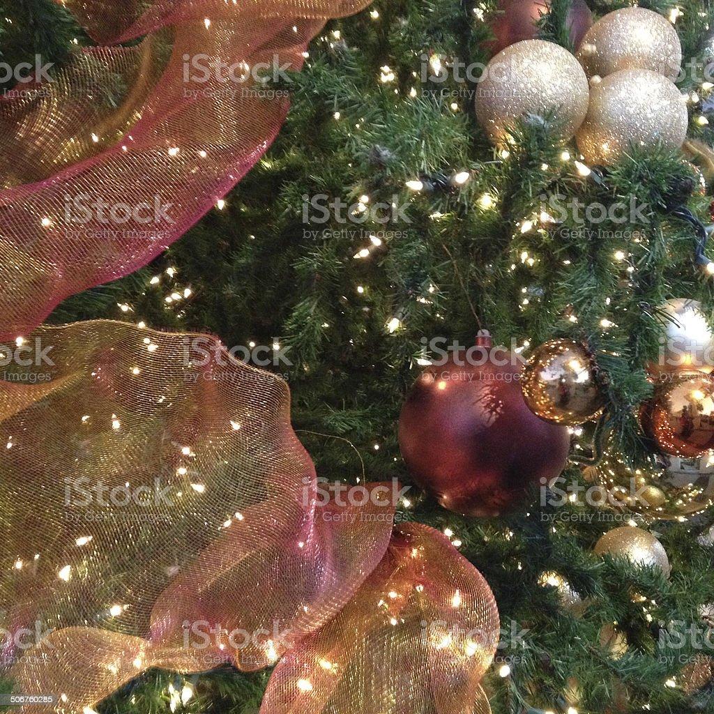 Holiday ornaments with ribbon on Christmas tree stock photo