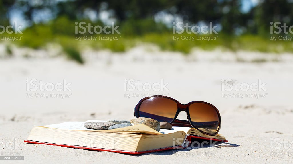 Holiday relax. The book and sunglasses on the beach stock photo