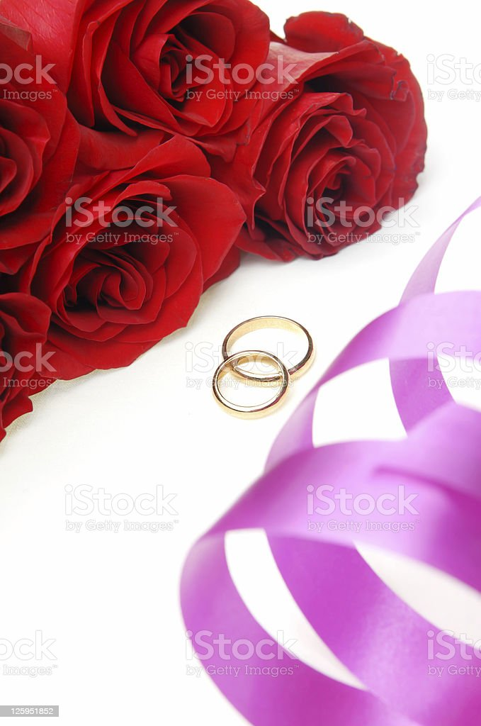 Holiday ribbon and wedding rings with flowers stock photo