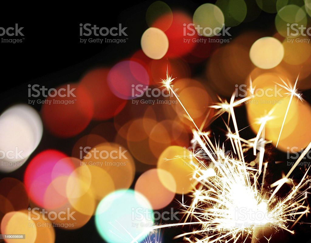 holiday sparkler and colorful lights stock photo