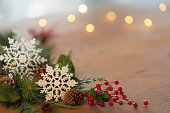 Holiday table decorations with snowflakes, pinecones, ribbon, and holly berries
