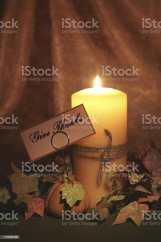 Burning candle with cord wrapped around it, autumn colored...