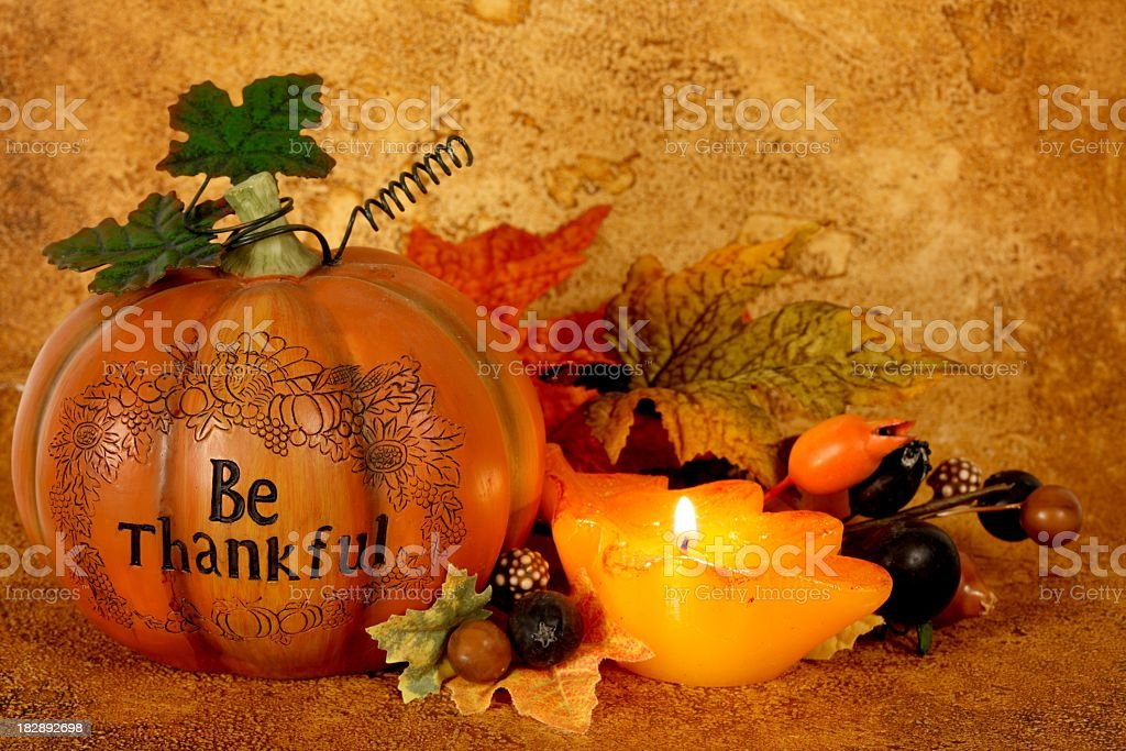 Thanksgiving still life with \'Be Thankful\' on orange pumpkin and leaf...