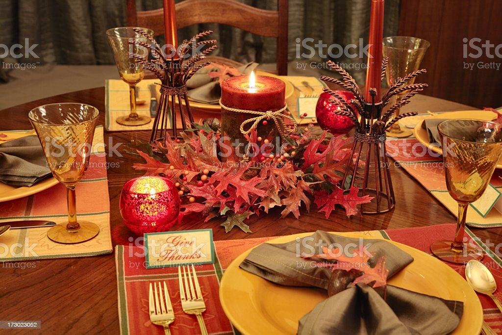 Thanksgiving table setting with autumn colored plates, napkins,...