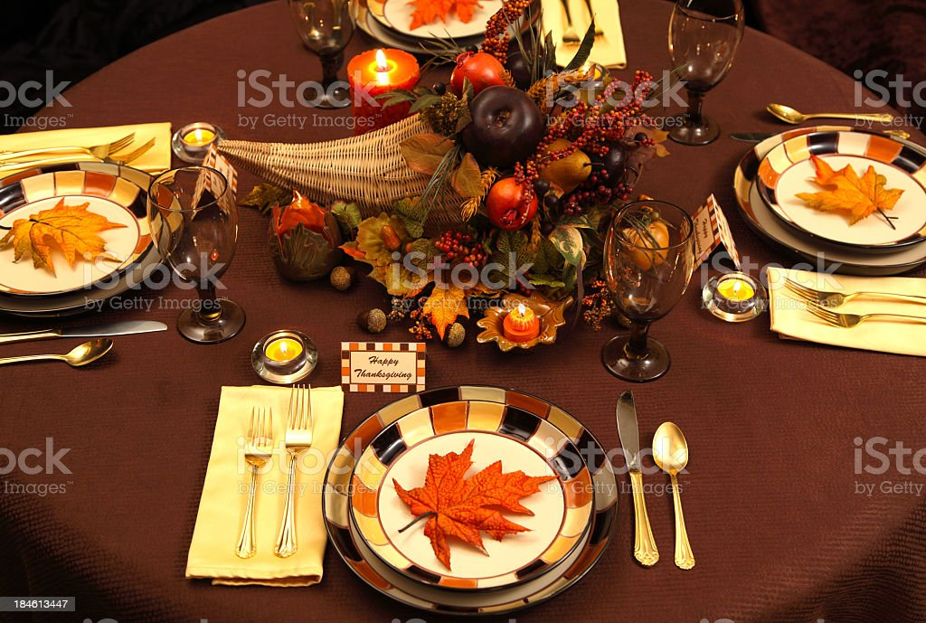 Thanksgiving Holiday table with cornucopia, candles, and leaves. Note...