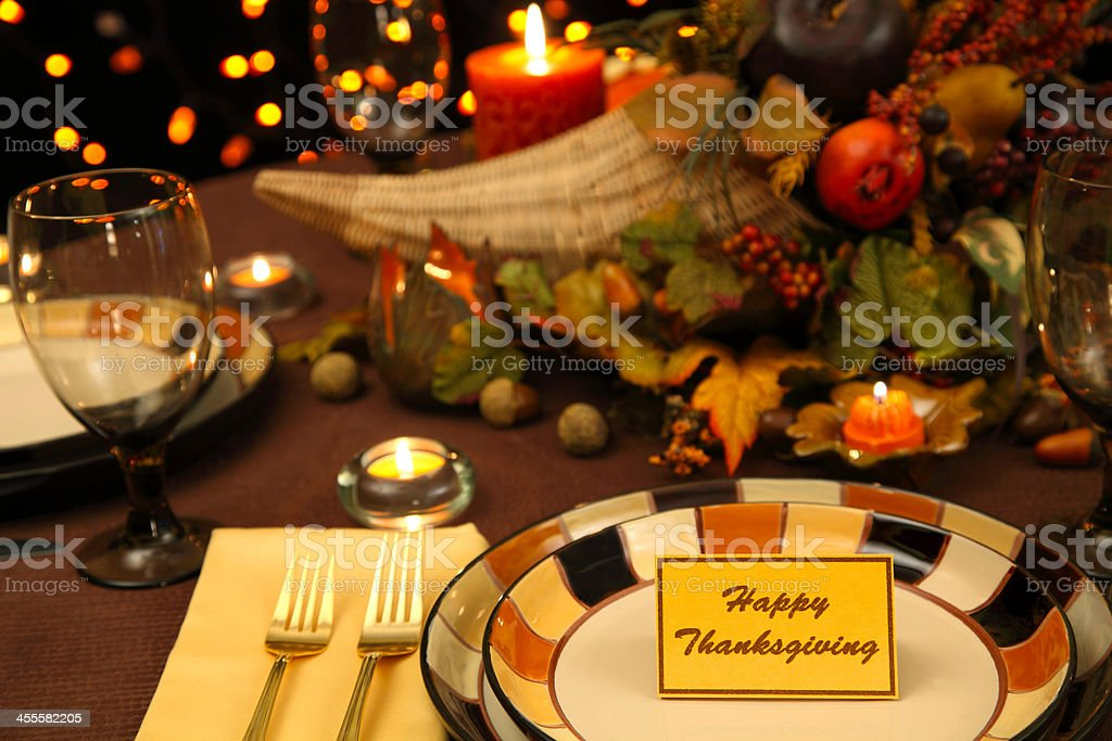 Thanksgiving Holiday table setting with cornucopia filled with autumn...