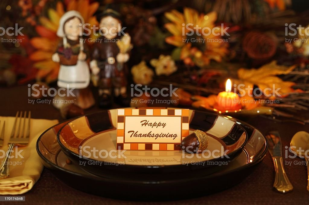 Thanksgiving Holiday table with a pilgrim couple, pumpkin candle, and...