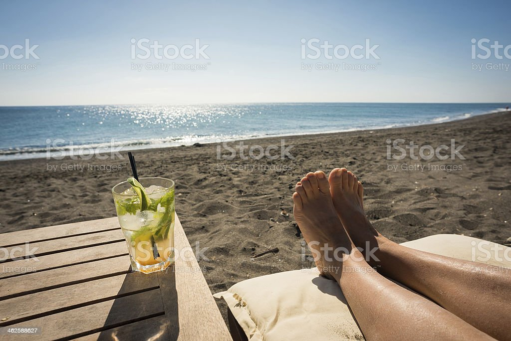 Holidaymaker enjoying a drink on beach stock photo