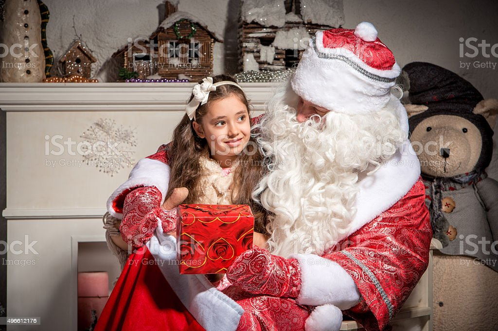 holidays and people concept - smiling little girl with santa stock photo