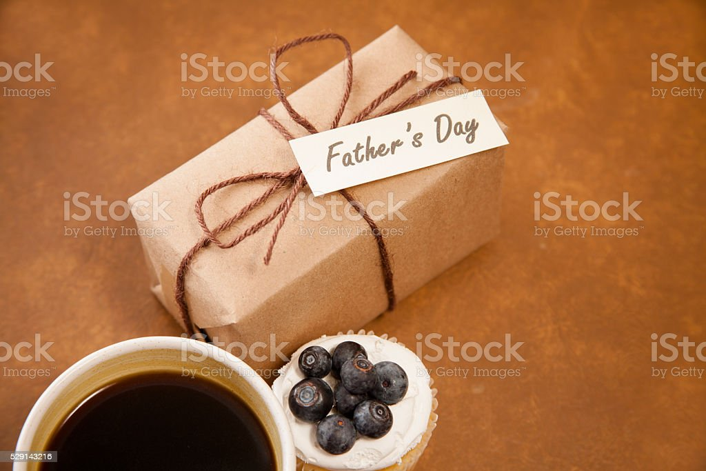 Holidays:  Father's Day wrapped gift for dad. Coffee, muffin. stock photo
