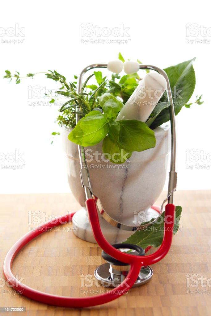 Holistic Medicine concept Photograph with plants in pestle and stethascope royalty-free stock photo
