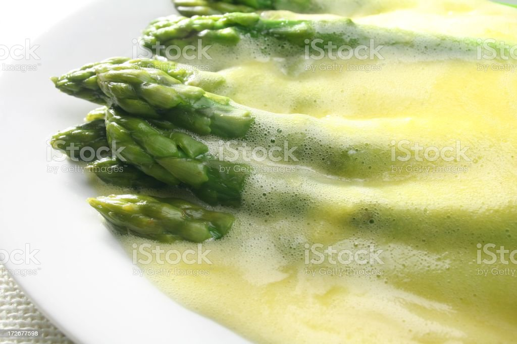 Hollandaise sauce over asparagus in a white dish stock photo