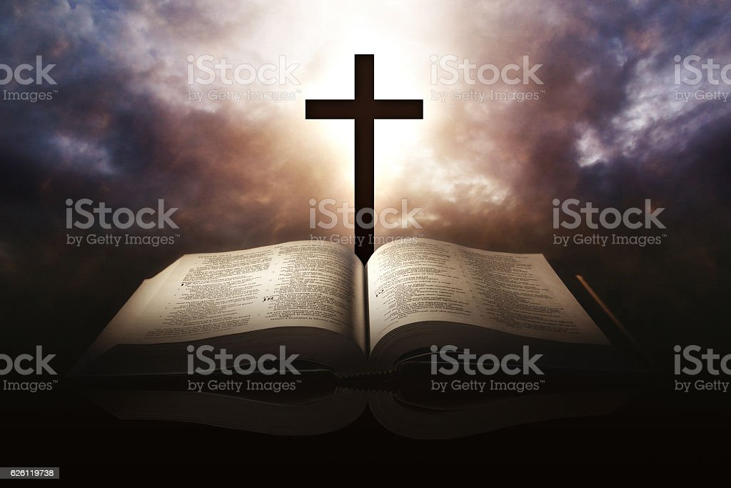 Holy Bible with a cross and a dramatic sky stock photo