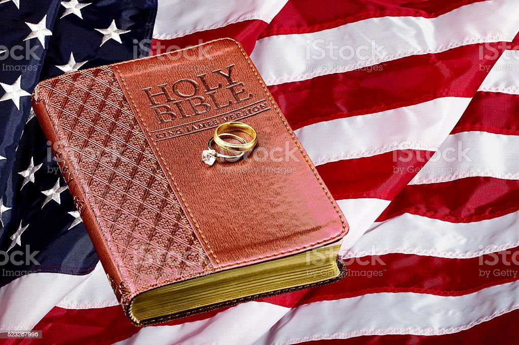 Holy Bible with Wedding Rings on American Flag Concept stock photo