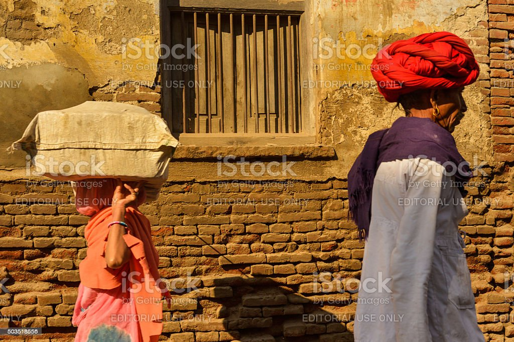 Holy Man and Woman Walking on Road in India. stock photo