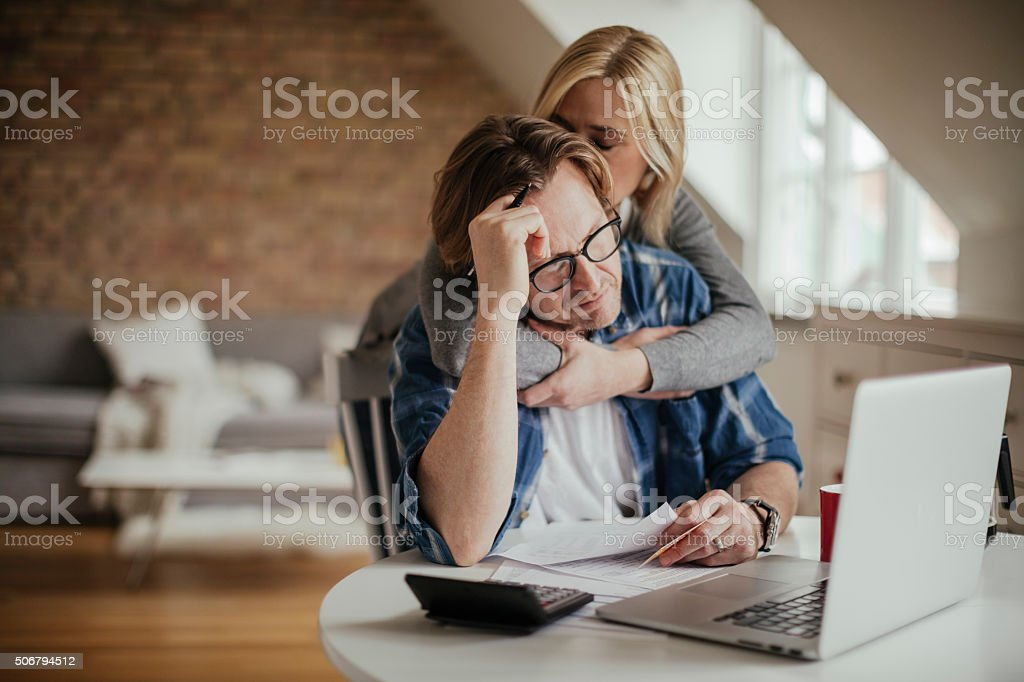 Photo of a worried mature couple calculating home finances