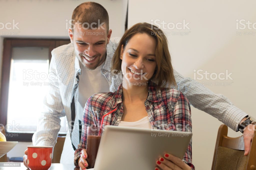 Young couple is checking their finances with a smile on a face. They...