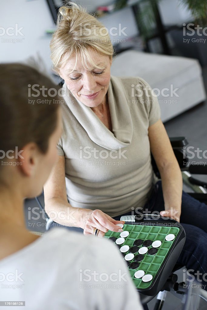 Home care with woman in wheelchair playing together royalty-free stock photo