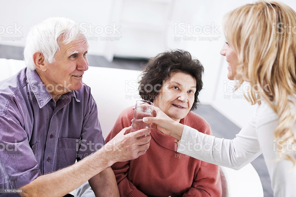 Home nurse helping a senior couple at home. She is giving a glass of...