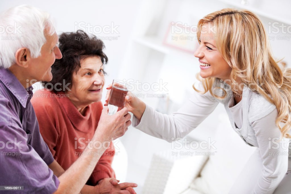 Home caregiver giving a senior man glass of water royalty-free stock photo