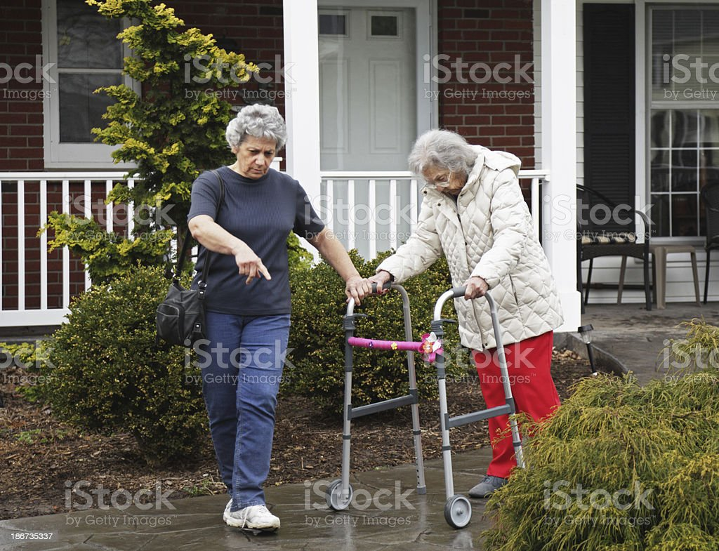 Home Caregiver Guiding Senior Woman With Dementia royalty-free stock photo
