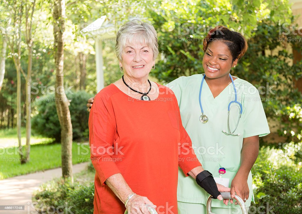 Home caregiver, nurse with senior adult patient outdoors. Nursing home. stock photo