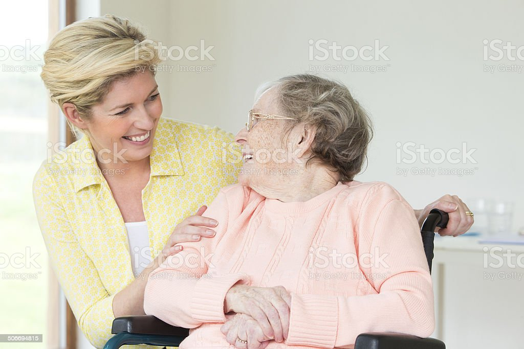 Portrait of senior woman and her young carer.