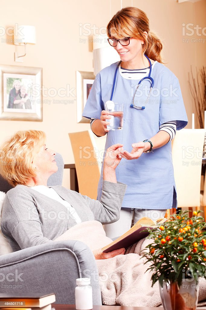 Portrait of senior woman sitting at home and home care nurse giving...