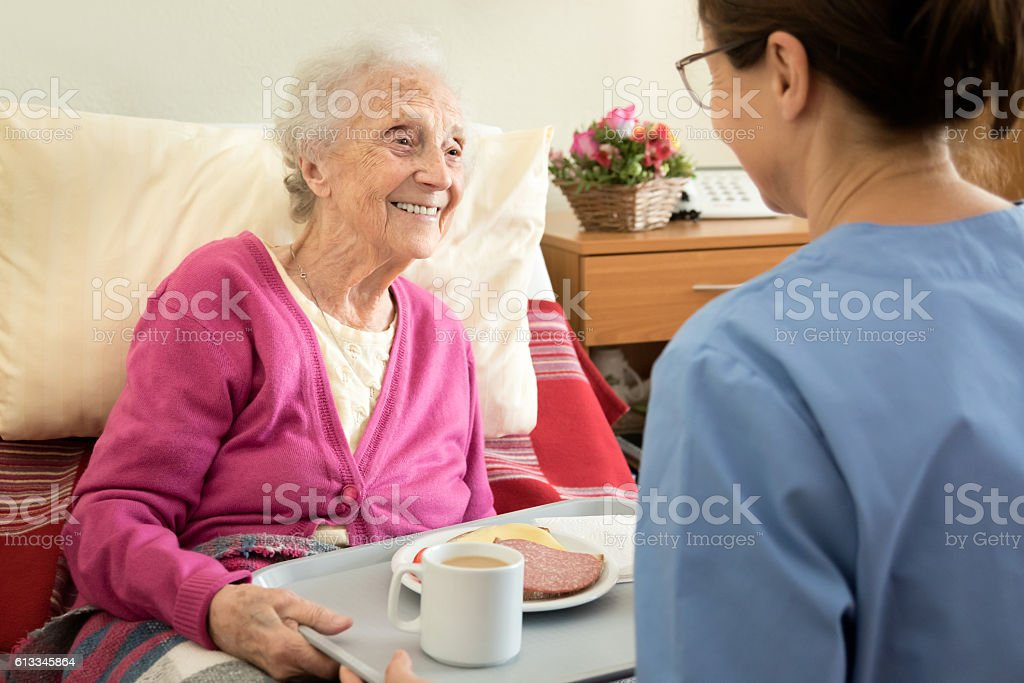 Home caregiver with senior adult woman, serving a meal