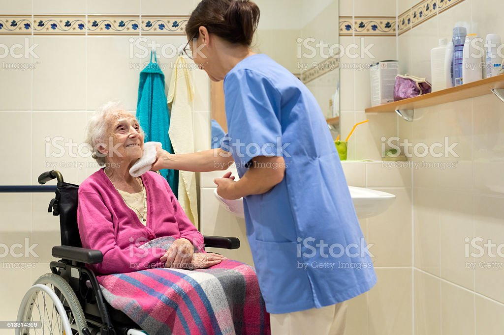 Home Caregiver with senior woman in bathroom stock photo