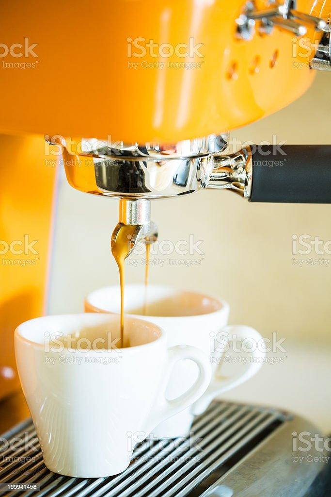 Home coffee machine brewing espresso to two small cups stock photo