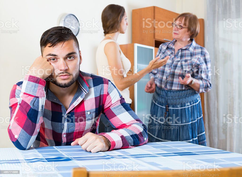 Home conflict at young family with mother stock photo