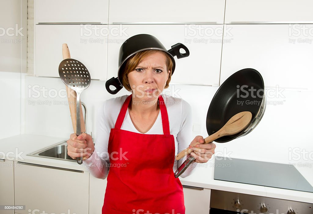 young attractive home cook woman in red apron at kitchen holding pan...