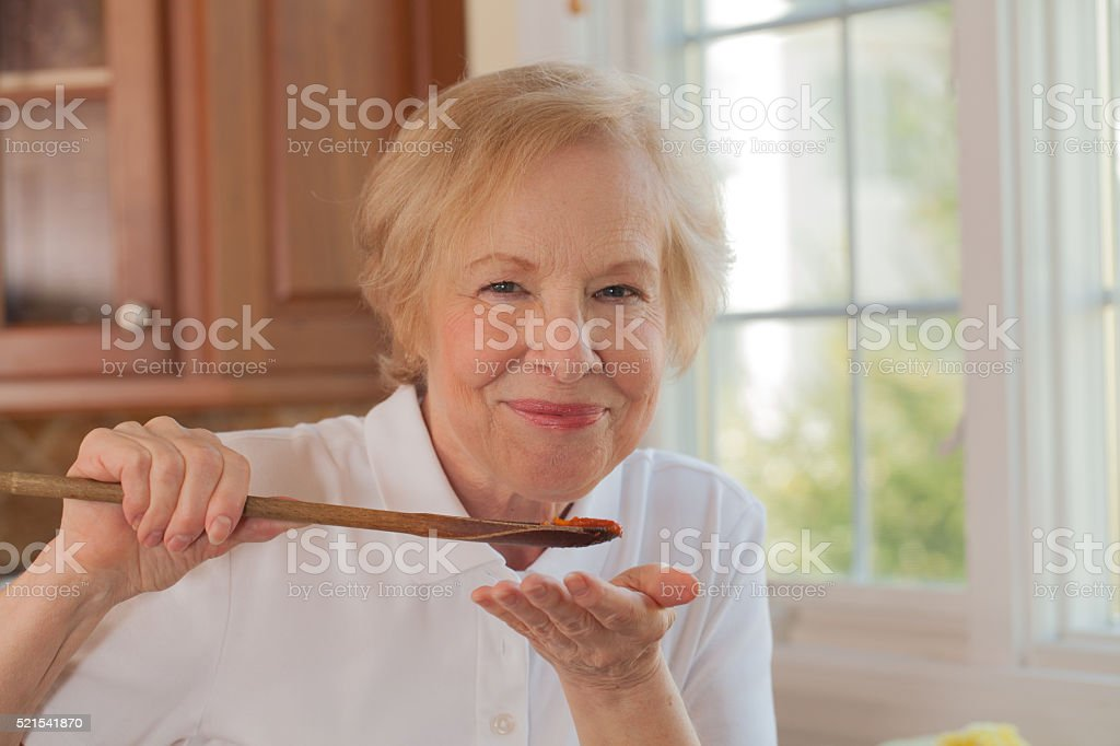 Home cooking: a senior woman tasting her sauce stock photo