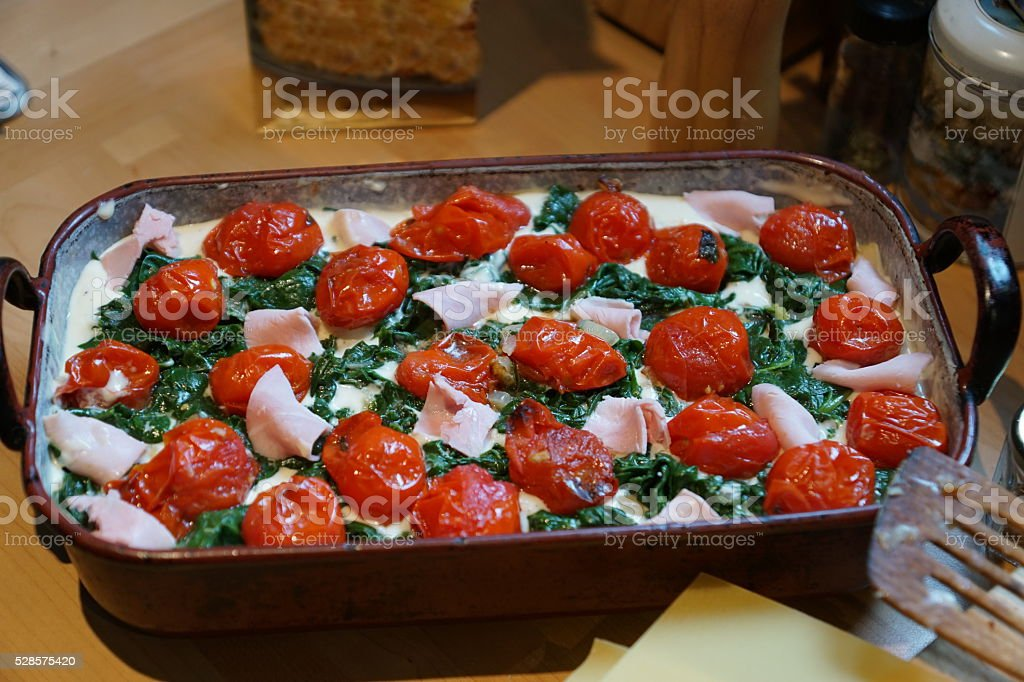 Home cooking - Spinach lasagne with Tomatoes, Ham and Garlic... stock photo