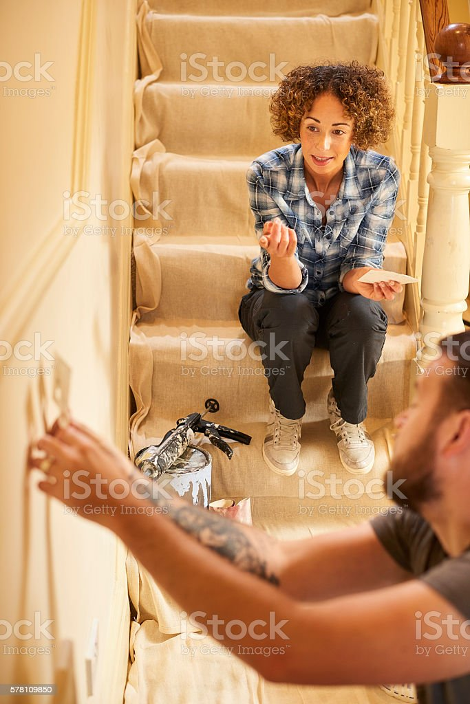 A young couple doing up their hallway in the old house they have...