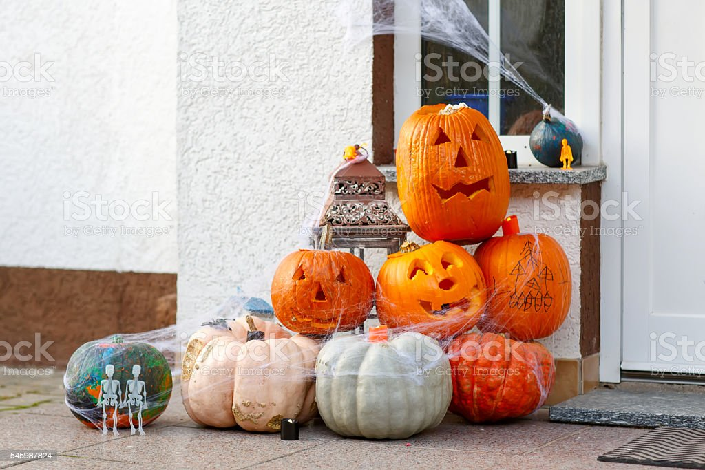 Home door decorated for halloween with scary jack-o-lantern pump stock photo