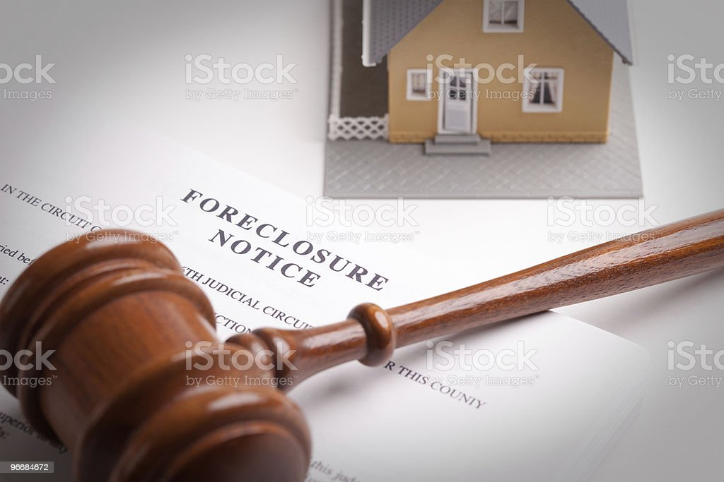 A home foreclosure notice underneath a gavel stock photo