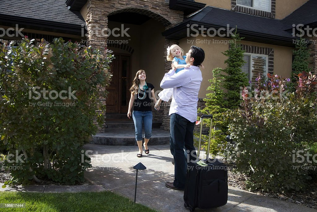 Home from a Business Trip- Dad and Daughter Hugging royalty-free stock photo