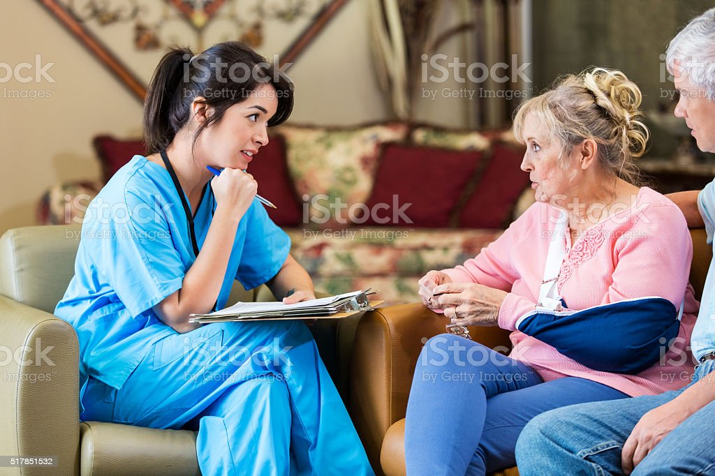 Home headlcare nurse talks with senior couple stock photo