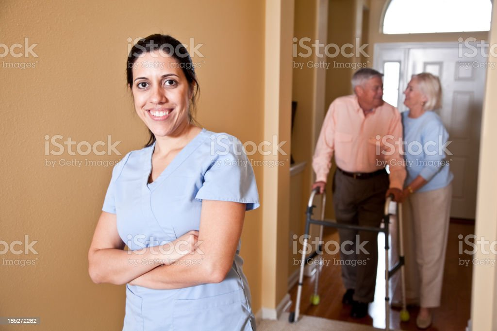 Home health aide - senior couple in background stock photo