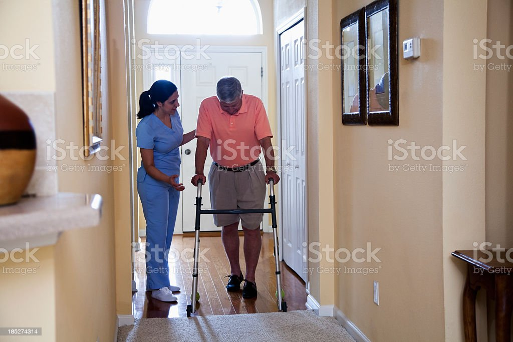 Home health aide with senior man using walker stock photo
