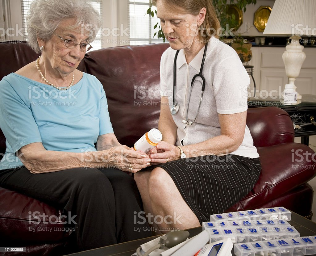 Home healthcare medical professional helps senior woman with medication stock photo