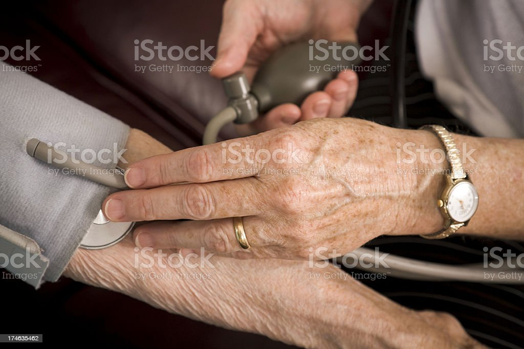 Home healthcare medical professional takes blood pressure of senior woman royalty-free stock photo