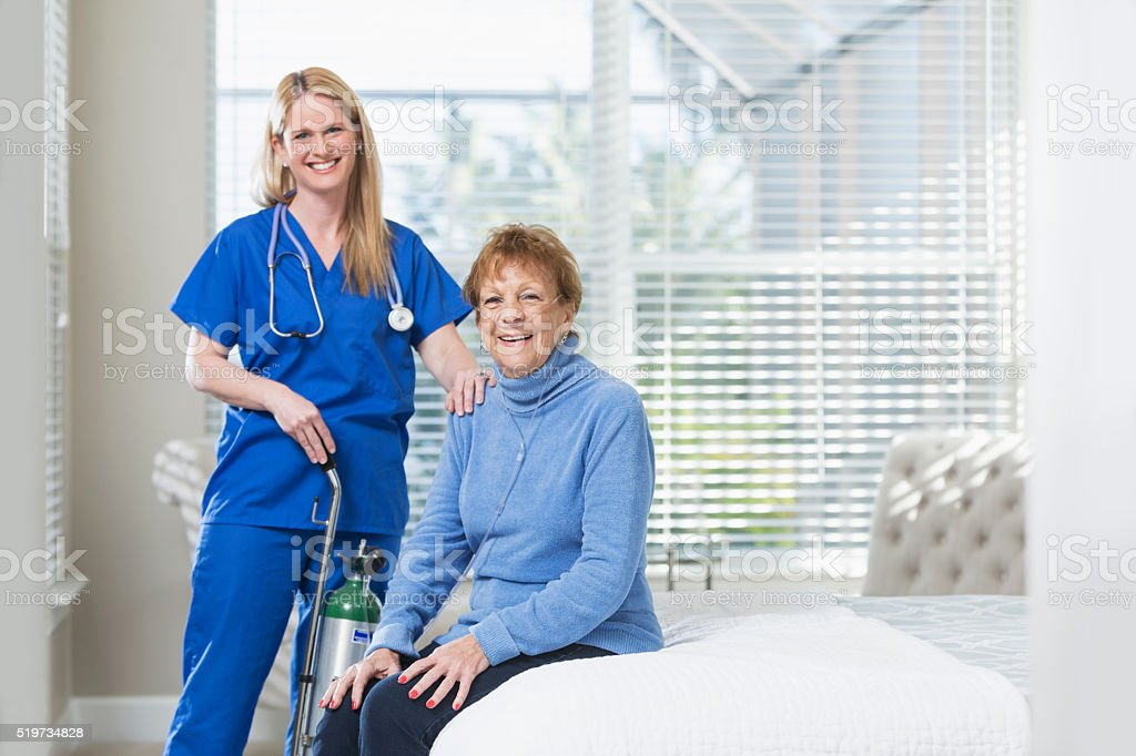 Home healthcare nurse and elderly woman with oxygen tank stock photo