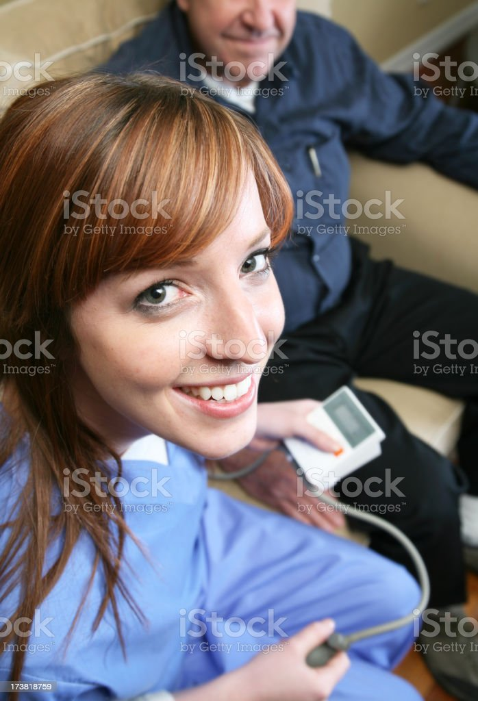 Home healthcare nurse checking blood pressure royalty-free stock photo